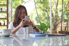 Asian woman using smart phone with feeling relax in modern cafe. A beautiful Asian woman using smart phone with feeling relax in modern cafe Stock Images