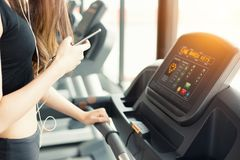 Asian woman using smart phone when workout or strength training. At fitness gym on treadmill. Relax and Technology concept. Sports Exercise and Health care Royalty Free Stock Images