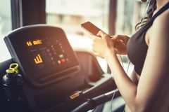Asian woman using smart phone when workout or strength training. At fitness gym on treadmill. Relax and Technology concept. Sports Exercise and Health care Stock Photo