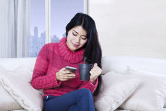Asian woman using a smartphone on couch. Image of Asian woman sitting on the couch while using a mobile phone and holding a cup of hot tea in the apartement Stock Photography
