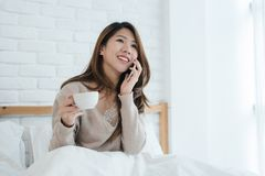 Asian woman using the smartphone on her bed while holding cup of coffee in the morning. royalty free stock photography