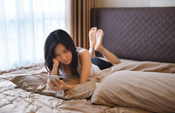 Asian woman using smartphone on pillow on bed Royalty Free Stock Photo