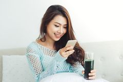 Asian woman using smartphone sitting on couch.  Royalty Free Stock Image