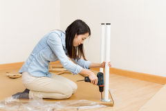 Asian woman using strew driver for assembling furniture Royalty Free Stock Photography