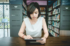 Asian woman using tablet pc on a wood table Royalty Free Stock Photos