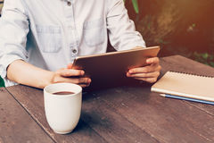 Asian woman using tablet on table and coffee in garden Stock Images
