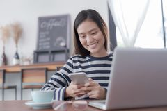 Asian woman are using their smartphone to buy product through social network. On ling stock image