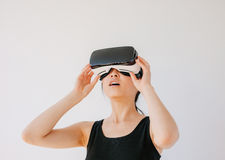 Asian woman using the virtual reality headset. And looking away. Female wearing VR goggles against grey background stock photography