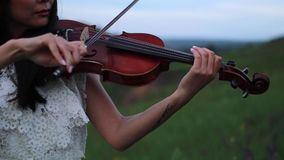 Asian woman violinist plays the violin on meadow at dusk. stock video footage