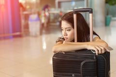 Asian woman waiting flight delay in airport. Hall her bored sitting wait long time early morning with baggage suitcase for travel transport Royalty Free Stock Photos
