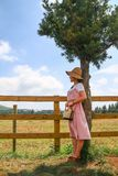 Asian woman waiting for someone standing by the fence in the ranch. Asian young woman waiting for someone standing by the fence in the ranch stock photos