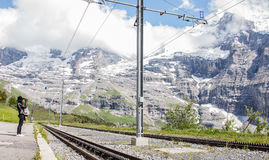 Asian woman waiting for Swiss railways train from Kleine Scheidegg at Wengernalp station with view of beautiful majestic swiss alp. Ine mountain ranges royalty free stock photos