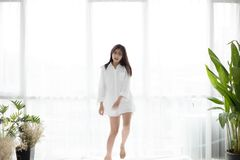 Asian woman wake up in her bed fully rested and open the curtain royalty free stock photos