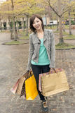 Asian woman walk and hold shopping bags Royalty Free Stock Photography