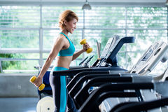 Asian woman walking on treadmill holding dumbbell Royalty Free Stock Image