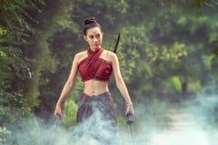 Asian woman warrior in Ayutthaya costume standing in smoke background