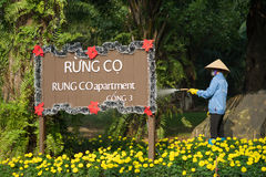 Asian woman watering a green and floral garden at Ecopark residential villa Stock Photos