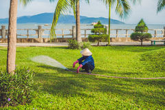 Asian woman watering a green and floral garden in the suburb of Nha Trang Royalty Free Stock Images