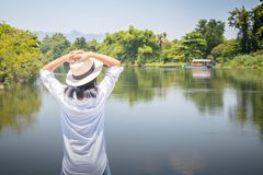 Woman looking forward to river with put her hands on head and she has feeling relax and happiness. royalty free stock images