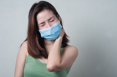 Asian Woman wear a mask are feeling neck pain. Royalty Free Stock Image