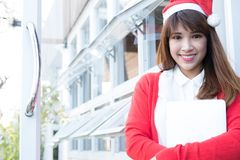 Woman wear santa hat holding laptop at her shop. asian female we. Asian woman wear santa hat holding laptop at her shop. asian female wear white shirt and red stock image
