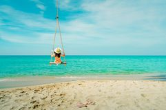 Asian woman wear swimwear and hat swing the swings at sand beach  and looking beautiful tropical paradise sea and sky on sunny day. Summer vacation. Summer stock photography