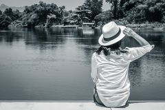 Asian woman wear weave hat and white shirt sitting on wooden terrace and looking forward to the river. royalty free stock photos