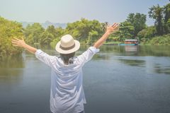 Asian woman wear weave hat and white shirt with standing on wooden terrace,. She looking forward to river with raising hands up and she has feeling relax and royalty free stock photo