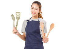 Asian Woman Wearing Apron And Showing Cooking Tools. Stock Photo
