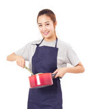 Asian Woman Wearing Apron And Showing Pot With Utensil. Asian Woman Wearing Apron And Showing Pot With Utensil On White Background Royalty Free Stock Photos