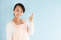 Asian woman wearing an apron with thumb up Royalty Free Stock Image