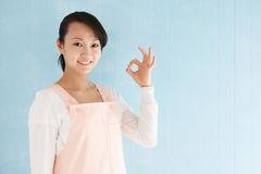 Asian woman wearing an apron to make a finger Stock Images