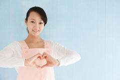 Asian woman wearing an apron to make a heart Royalty Free Stock Image