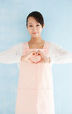 Asian woman wearing an apron to make a heart Royalty Free Stock Photos