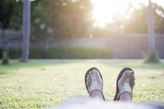 Asian woman wearing bare foot in brown slippers lay on green grass for relaxing. With sun light and bokeh background Stock Images