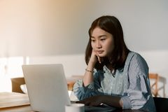 Asian woman Wearing a blue striped shirt sitting in front of a laptop computer Take her hands, feet, chin With the expression stock image