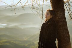 Winter Travel. Asian woman wearing coat standing by the mountain,Cold weather,fog on hills,Winter hiking,Travel in Chiang Mai,Thailand Royalty Free Stock Photography