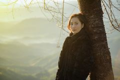 Winter Travel. Asian woman wearing coat standing by the mountain,Cold weather,fog on hills,Winter hiking,Travel in Chiang Mai,Thailand Stock Photography