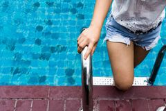 Asian woman wearing denim shorts on swimming pool ladder. Asian woman wearing blue denim shorts on swimming pool steel ladder Stock Images