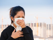Asian woman wearing face mask and coughing. By pollution Stock Image