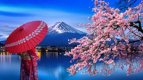 Asian woman wearing japanese traditional kimono at Fuji mountain and cherry blossom, Kawaguchiko lake in Japan