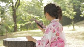 Asian woman wearing a kimono in front of Japanese wooden windows stock footage