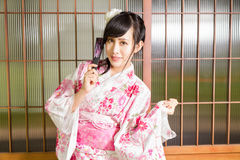 Asian woman wearing a kimono in front of Japanese stock image