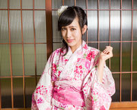 Asian woman wearing a kimono in front of Japanese wooden windows royalty free stock photography