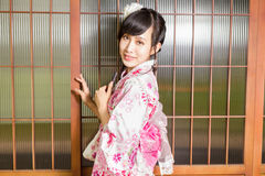 Asian woman wearing a kimono in front of Japanese wooden windows Royalty Free Stock Photo