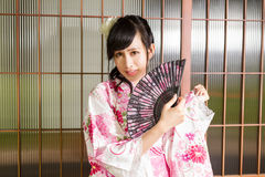 Asian woman wearing a kimono in front of Japanese wooden windows Royalty Free Stock Photos