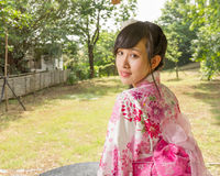 Asian woman wearing a kimono in Japanese garden Royalty Free Stock Photo