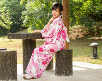 Asian woman wearing a kimono sitting in Japanese garden Stock Images