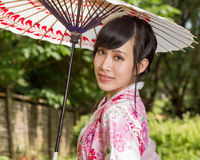 Asian woman wearing a kimono sitting in Japanese garden royalty free stock images