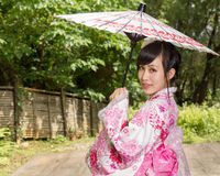 Asian woman wearing a kimono sitting in Japanese garden Stock Photo